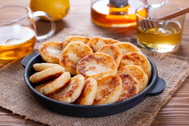 Hüttenkäsepfannkuchen mit honig auf einem teller auf hölzernem hintergrund. frühstück