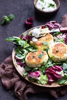 Hüttenkäsepfannkuchen mit käse und kräutern, serviert mit salatmischung und saurer sahne.