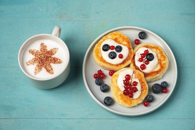Hüttenkäsepfannkuchen mit roter johannisbeere und blaubeere, kaffee in einer tasse.