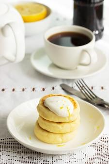 Hüttenkäsepfannkuchen mit sauerrahm und zitronenschale, serviert mit tee. selektiver fokus.