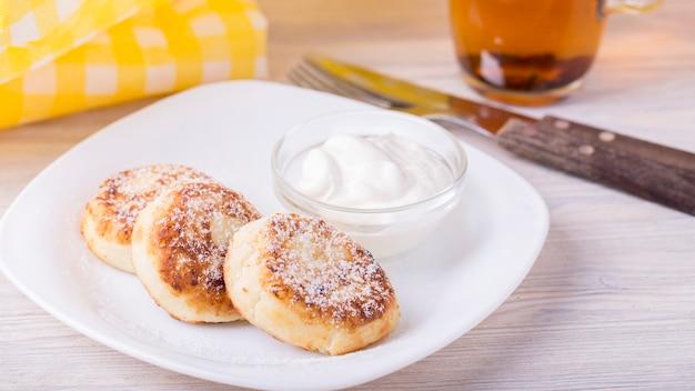 Hüttenkäsepfannkuchen mit saurer sahne und puderzucker. copyspace