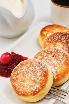 Hüttenkäsepfannkuchen oder gebratene hüttenkäsepfannkuchen, mit puderzucker bestreut, auf einem teller mit preiselbeermarmelade und sauerrahm.