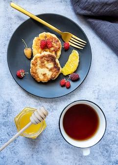 Hüttenkäsepfannkuchen oder russisches syrniki mit beeren und honig und eine tasse tee zum frühstück