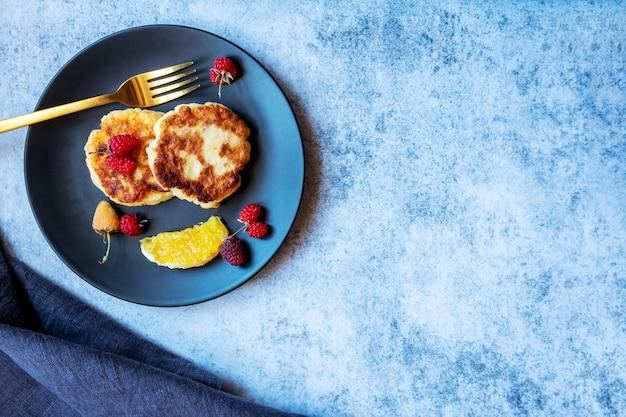 Hüttenkäsepfannkuchen, russisches syrniki, auf einem schwarzen teller mit beeren, orange. gesundes frühstück reich an kalzium. speicherplatz kopieren