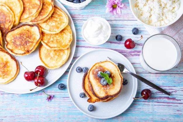 Hüttenkäsepfannkuchen (syrniki). hausgemachte käsekuchen aus hüttenkäse mit sauerrahm, beeren und milch. traditionelles russisches gericht. nahansicht.