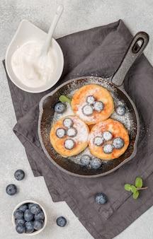 Hüttenkäsepfannkuchen, syrniki, quarkstückchen mit frischen heidelbeeren, puderzucker und sauerrahm in einer gusseisernen pfanne