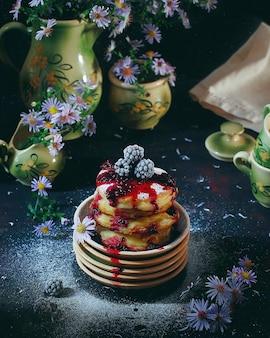 Hüttenkäsepfannkuchen, syrniki, quarkstückchen mit gefrorenen beeren (blackberry) und puderzucker in einer weinleseplatte. gourmet-frühstück