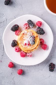 Hüttenkäsepfannkuchen und puderzucker, quark-krapfen-dessert mit himbeer- und brombeerbeeren in platte nahe heißer teetasse mit zitronenscheibe auf steinbeton, draufsicht