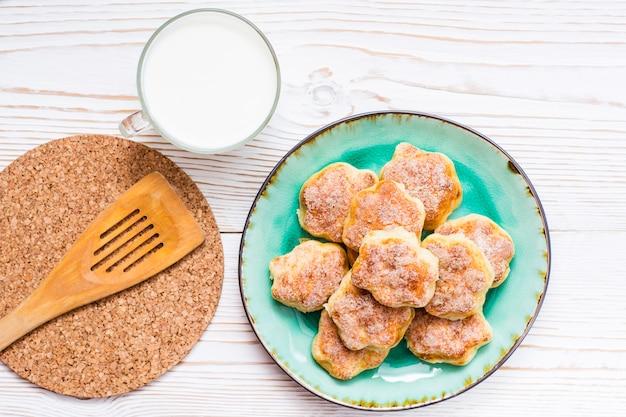 Hüttenkäseplätzchen besprüht mit zucker auf einem teller und einer tasse milch