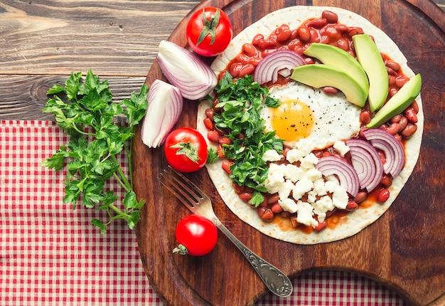 Huevos rancheros frühstückspizza mit tomaten, zwiebeln und petersilie auf rustikalem holztisch. draufsicht.