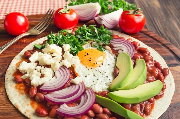 Huevos rancheros frühstückspizza mit tomaten, zwiebeln und petersilie auf rustikalem holztisch. selektiver fokus.