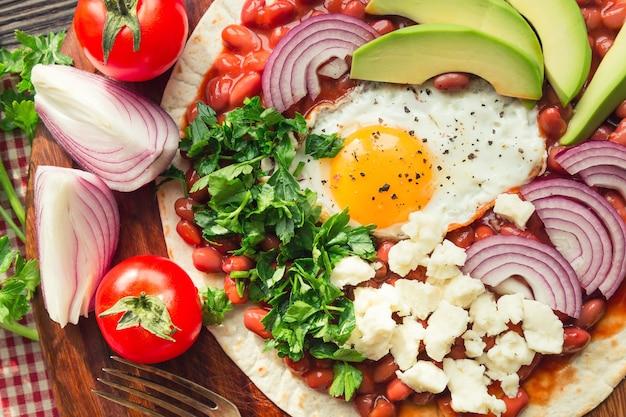 Huevos rancheros frühstückspizza mit tomaten, zwiebeln und petersilie