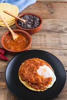 Huevos rancheros gericht, mexikanisches frühstück auf holzbasis. mexikanische küche.