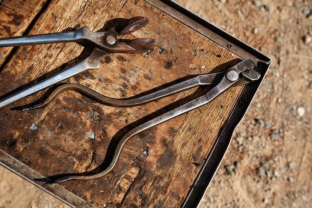 Hufeisenpferdewerkzeuge auf einem schmutzholz