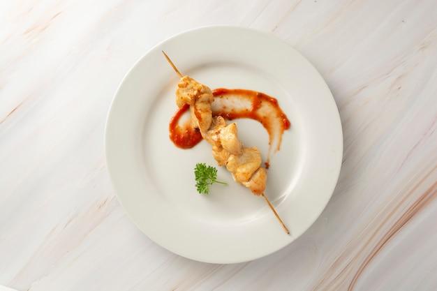 Huhn auf bambusaufsteckspindelkebab in der weißen platte, heller marmorhintergrund. diät fettarmes essen.