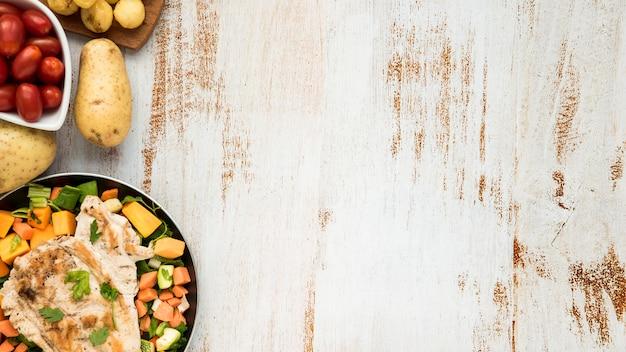 Huhn auf bratpfanne und gemüse auf grunge malte schreibtisch