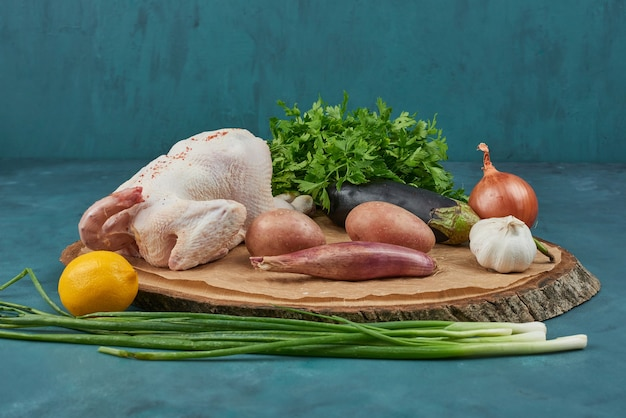 Huhn auf einem holzbrett mit gemüse.