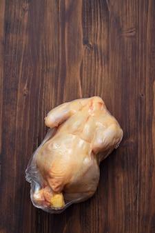 Huhn im vakuumbeutel auf holzoberfläche
