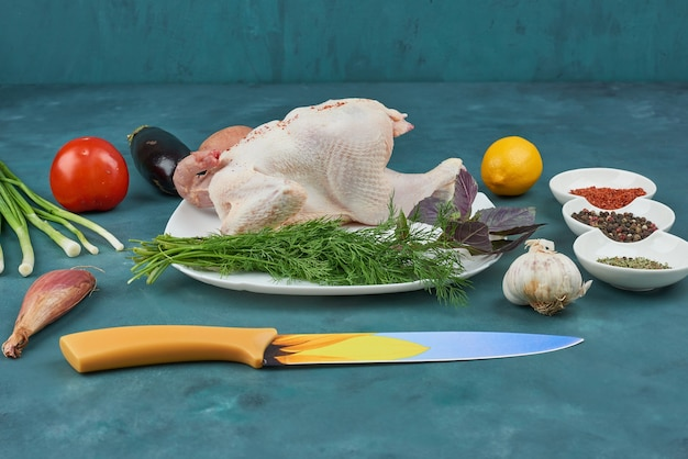 Huhn in einem weißen teller mit kräutern und gewürzen.