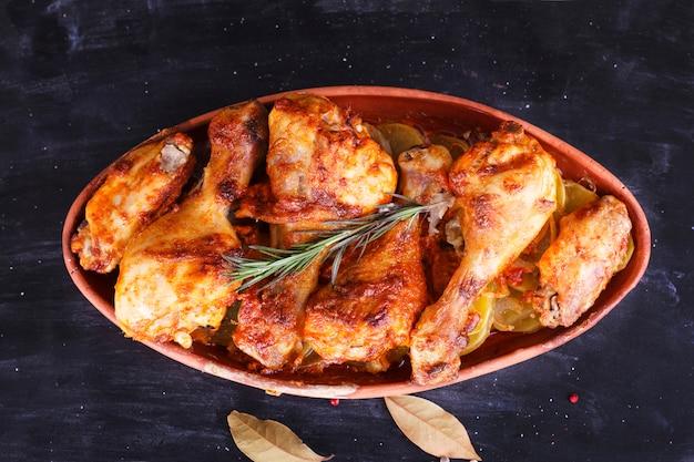 Huhn in paprikasoße im ofen in der keramik gebacken. hühnerbeine und flügel