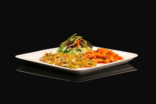 Huhn mit currysauce und nudeln mit roter sauce und salat in weißer platte