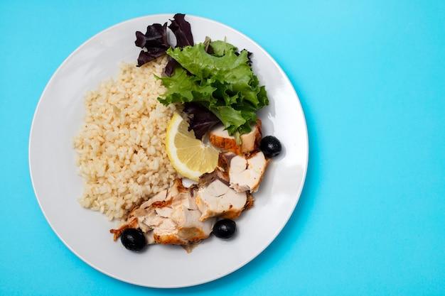 Huhn mit gekochtem reis und salat auf weißem teller