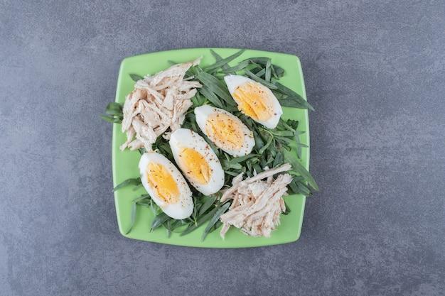 Huhn mit gekochten eiern auf grüner platte.