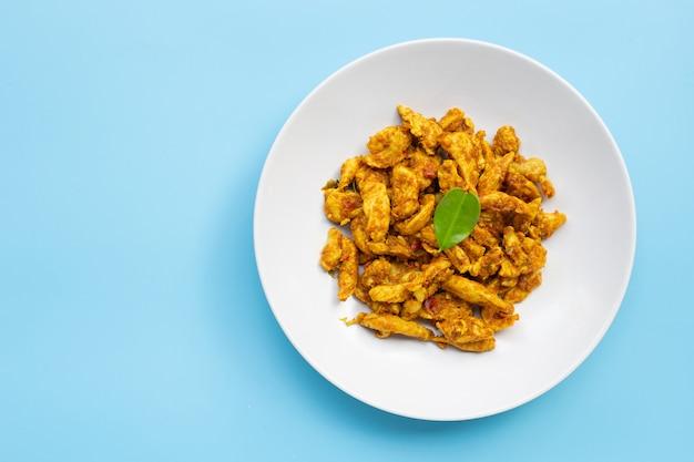 Huhn mit gelber curry-paste auf blauem hintergrund. speicherplatz kopieren