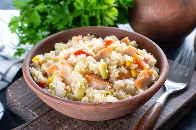 Huhn mit gemüse und quinoa auf teller auf holztisch