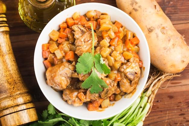 Huhn mit kartoffel und karotte im curry,
