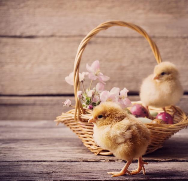 Huhn mit ostereiern auf hölzernem hintergrund