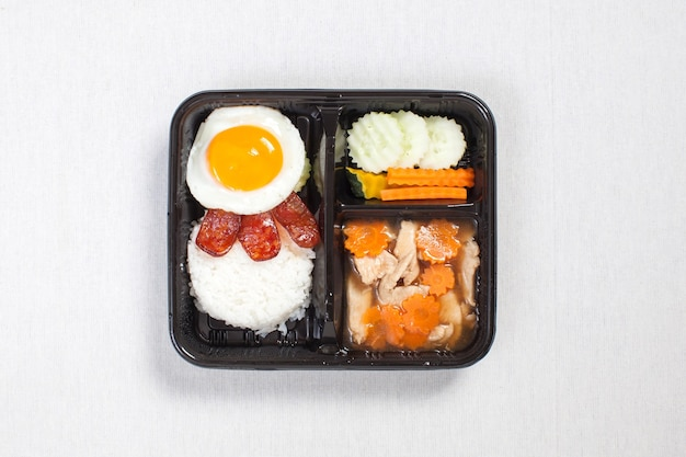 Huhn mit soße mit spiegelei auf reis in eine schwarze plastikbox gelegt, auf eine weiße tischdecke, lebensmittelbox, thailändisches essen gelegt.