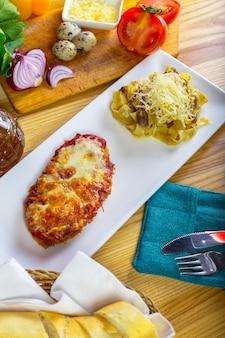 Huhn parmigiana und spaghettis nah oben auf einer platte auf dem tisch.