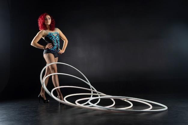Hula-hoop-mädchen führt zirkusartistin in einem künstlerischen kostüm auf