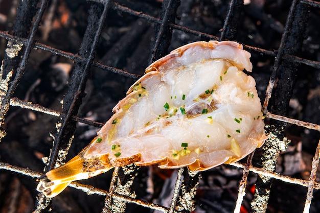 Hummer gebraten auf einem grill auf heißen kohlen nahaufnahme. hummer gegrillte gegrillte meeresfrüchte in bbq flames.
