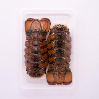 Hummerschwanz, hochwertige gefrorene und aufgetaute meeresfrüchte, verpackt in einem tablett mit iqf-verfahren, individuell schnell gefroren für das design der lebensmittel- und meeresfrüchteindustrie.