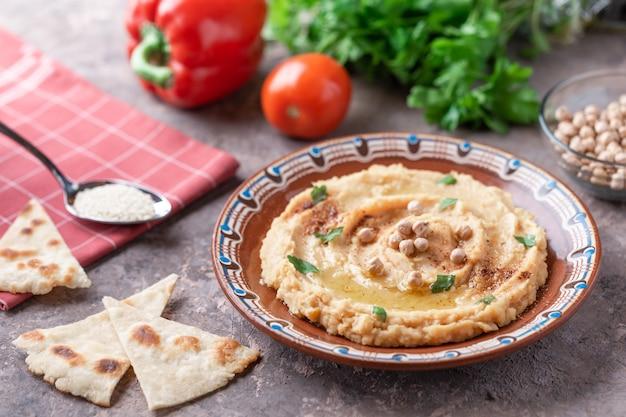 Hummus in der braunen lehmplatte