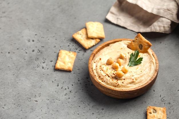 Hummus in einem holzteller mit petersilie und croutons
