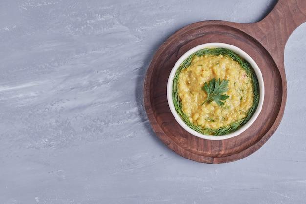 Hummus in einer weißen tasse mit kräutern auf einem holzbrett.