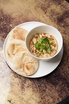 Hummus mit avocado und kräutern. weißer teller mit hummus und pfannkuchen auf dem tisch