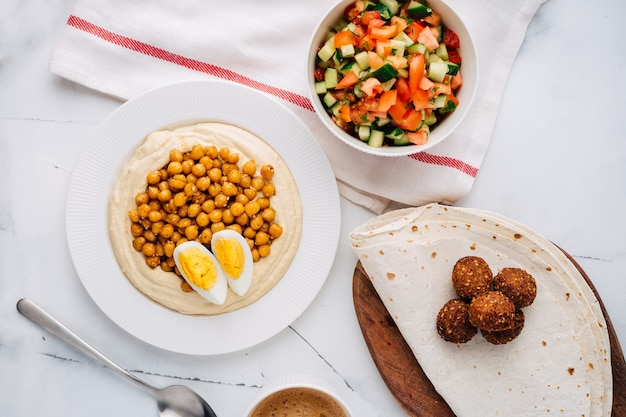 Hummus mit gekochten kichererbsen, ei, falafel, lavash und salat. flache lage. draufsicht