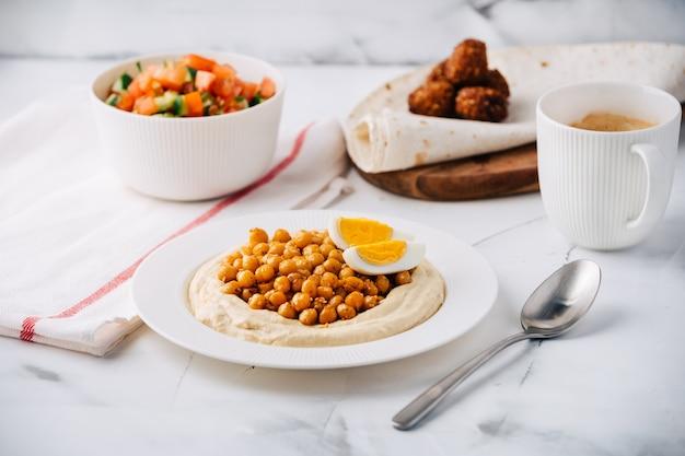 Hummus mit gekochten kichererbsen, ei, falafel, lavash und salat und kaffee. frühstück. gericht aus dem nahen osten