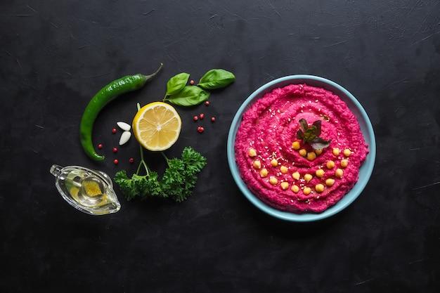 Hummus mit rote beete auf einem schwarzen küchentisch