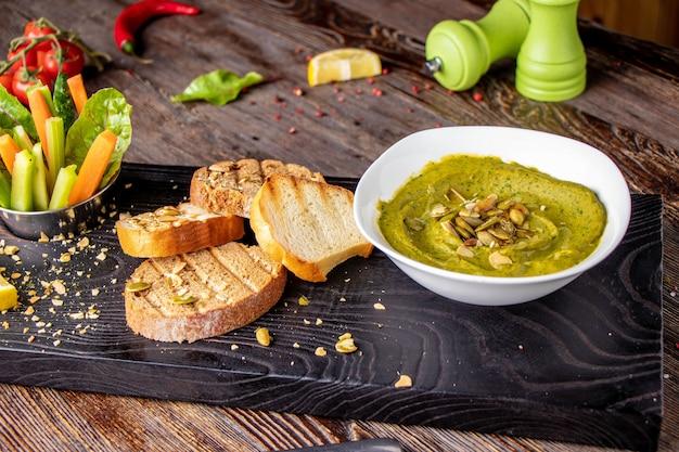 Hummus mit spinat, avocado und kürbiskernen in einer schüssel auf einem hölzernen brett und einem bruschetta, orientalische küche