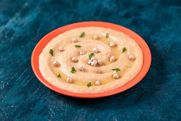 Hummus zu einem orangefarbenen teller.