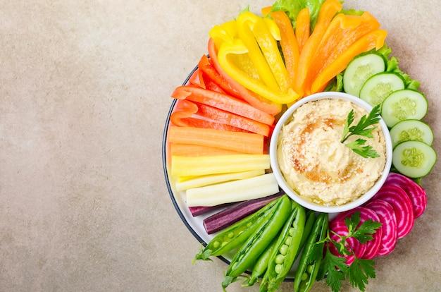 Hummusplatte mit verschiedenen gemüsesnacks. gesundes veganes und vegetarisches essen. draufsicht, flache lage, kopierraum.