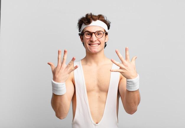 Humorvoller sportmann, der lächelt und freundlich aussieht, die nummer zehn oder zehn mit der hand nach vorne zeigt, herunterzählt