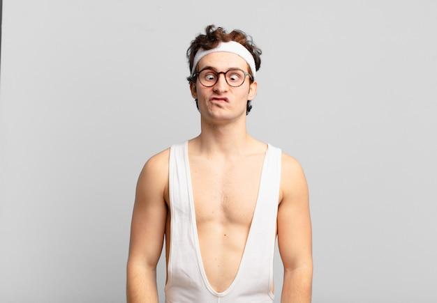 Humorvoller sportmann, der mit einem albernen, schielenden ausdruck albern und lustig aussieht, scherzt und herumalbert