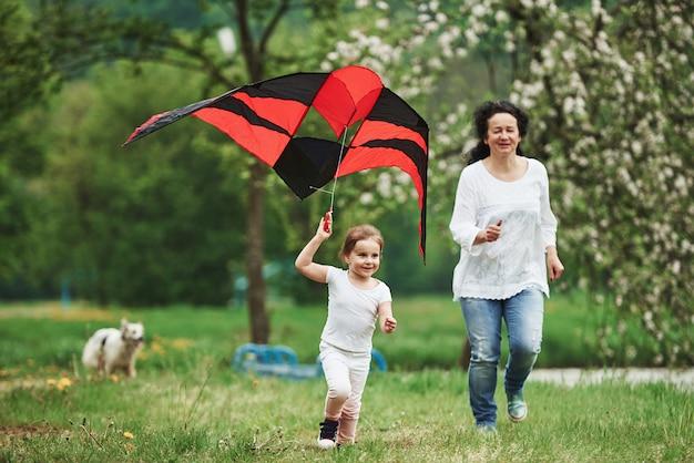 Hund ist im hintergrund. positives weibliches kind und großmutter, die mit rotem und schwarzem drachen in den händen draußen laufen