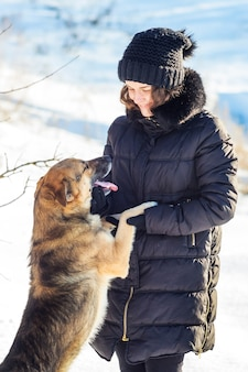 Hund steht auf hinterbeinen in der nähe von mädchen und schaut während des winterspaziergangs auf ihr gesicht